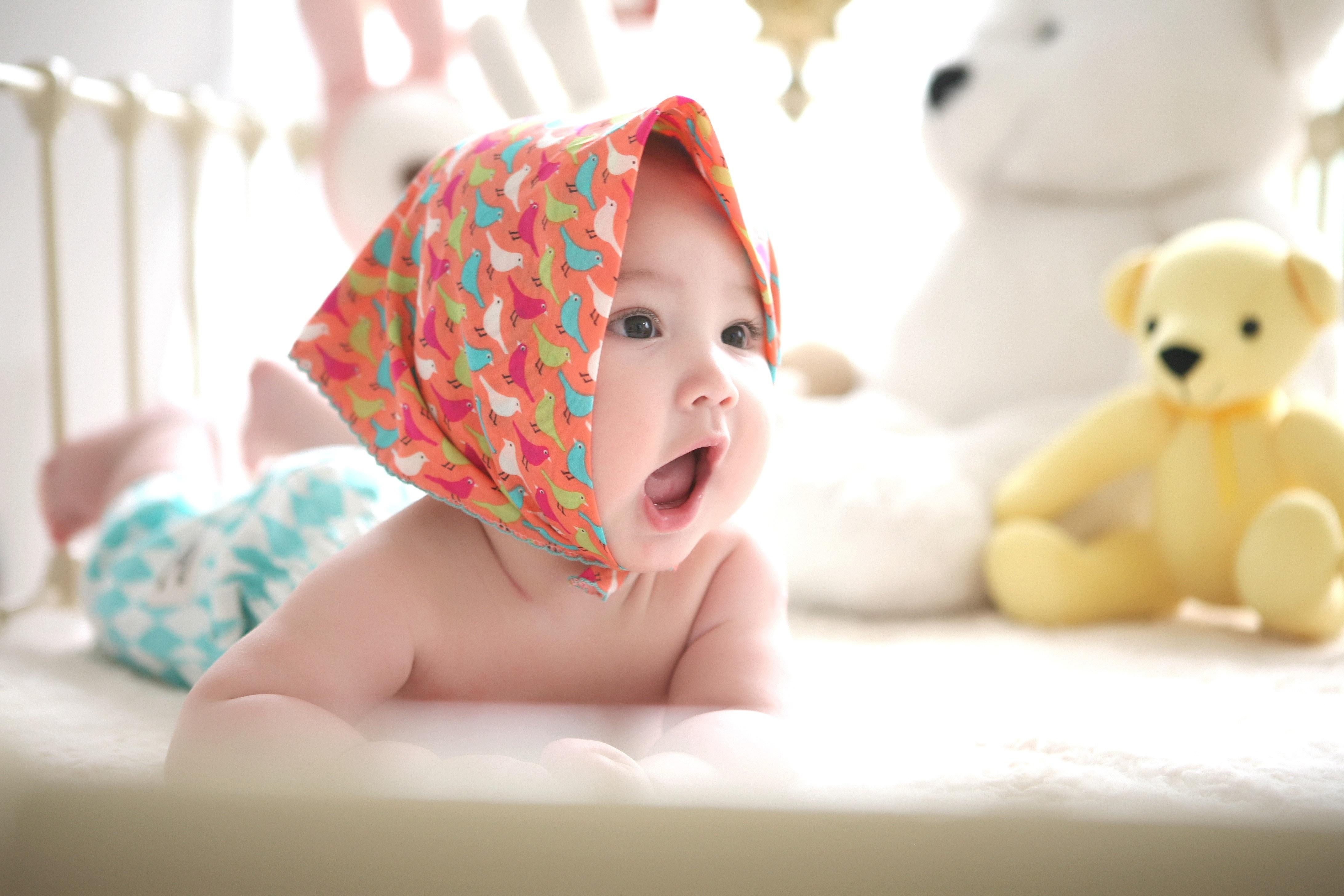 Младенец в кроватке с мягкими игрушками